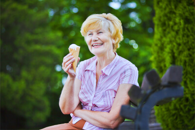 happy old lady sitting on bench in the park